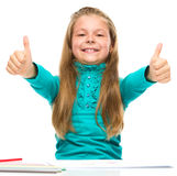 Little girl is showing thumb up sign Stock Images