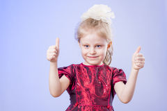 Little girl showing thumbs up. Little girl in dark red dress showing two thumbs up Stock Photos