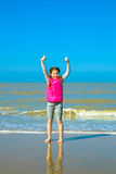 Little girl showing thumbs up on the shore Stock Image