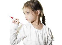 Little girl shows  ballpoint pen Stock Images