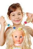 Little girl shows dolls braids Royalty Free Stock Image