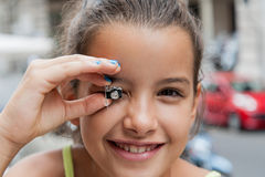Little girl shows earring reflex Stock Photography