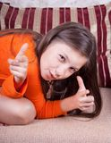 The little girl shows a finger.  Royalty Free Stock Photography