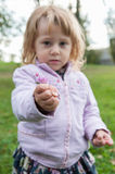Little girl shows a flower just picked Stock Photography