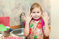 Little girl shows hands after washing dishes Royalty Free Stock Images