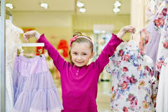 Little girl shows hangers with skirt and blouse Royalty Free Stock Image