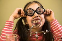 Little Girl Shows her teeth in Magnifier. Child Scientist. In glasses stock photography