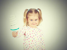 Little girl shows a large energy-saving light bulbs. Royalty Free Stock Images