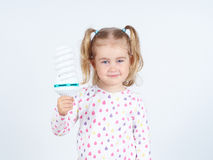 Little girl shows a large energy-saving light bulbs. Royalty Free Stock Photography