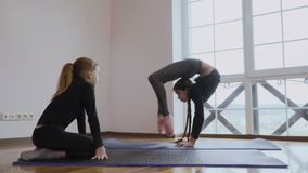 Little girl shows a sister her flexibility. Two girls makes a sport exercises at the floor in front of window. The girl show her sister how to make a bridge pose stock video