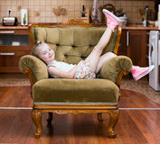 Little girl shows sneakers. On chair Royalty Free Stock Photo