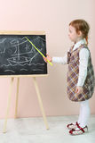 Little girl shows by yellow pointer ship at chalkboard Stock Photography