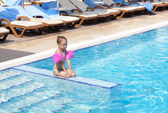 Little girl on the side of the pool. Royalty Free Stock Photography