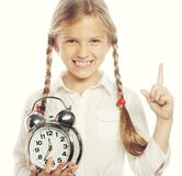 Little girl with a silvered alarm-clock Stock Image