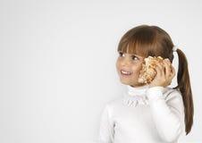 Little girl simulate phone calling. Little girl with cockleshell simulate phone call Stock Photo