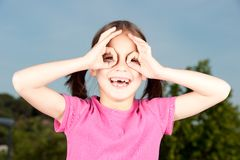 Little girl simulating binoculars Stock Photo