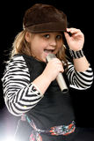 Little Girl Singing. A stylish little girl is sing into a microphone, shot with a backlight Stock Images