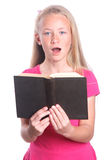 Little girl singing with book. Portrait of a cute little blond Caucasian preteen girl child singing a song with holding a black old book in her hands. Image Stock Photos