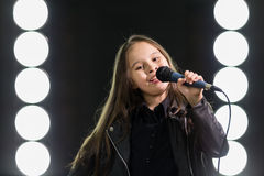 Little girl singing in front of stage lights Royalty Free Stock Photography