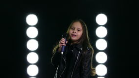 Little girl singing in front of stage lights stock footage
