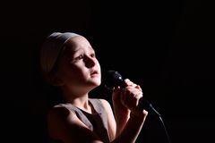 Little girl singing. On the microphone Stock Photo