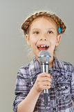Little girl singing into microphone Royalty Free Stock Image