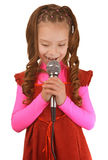 Little girl singing into microphone Stock Photos