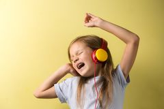 Little girl singing in headphones royalty free stock photography