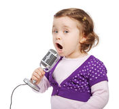 Little girl sings into the microphone. Royalty Free Stock Photography