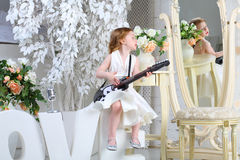 A little girl sings and plays guitar Royalty Free Stock Photography