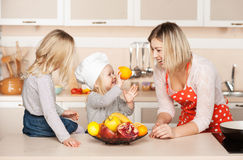 Little girl with sister showing orange to their Stock Image