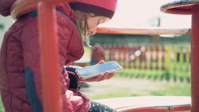 Little girl sit on a carousel in the playground and using app on smartphone stock footage