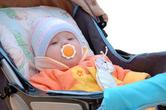Little girl sit in carriage. Little girl with baby's dummy sit in carriage. In cap and bright orange jacket royalty free stock image
