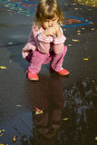 Little girl sit down near pool after rain Royalty Free Stock Photos