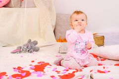 Little girl sit on flour among paper harts, sucking fingers. Looking up Royalty Free Stock Images