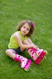 Little girl sit on the grass with roller skates Royalty Free Stock Image