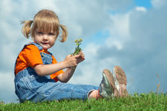 Little girl sit on green grass under sky. With clouds Stock Photo