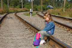 The little girl sit on railway rails. The little girl sit with a backpack on railway rails Royalty Free Stock Photos