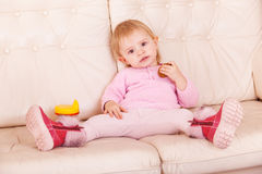 Little girl sit on sofa Royalty Free Stock Images