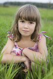 Little girl sitiing in meadow Royalty Free Stock Image