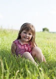 Little girl siting on the green grass Stock Photography