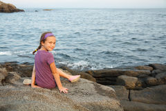 Little girl siting by the sea Royalty Free Stock Photo