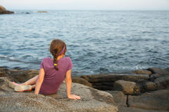 Little girl siting by the sea Stock Photos