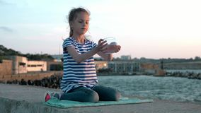 Little girl sits against backdrop city jetty of sea view at sunset .takes small fishbowl and looks at small fish. Concept recreati. Little girl sits against stock video