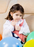 Little girl sits in an armchair Stock Photography