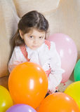 Little girl sits in an armchair Stock Photo