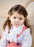 Little girl sits in an armchair Royalty Free Stock Photos