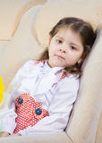Little girl sits in an armchair Royalty Free Stock Photo
