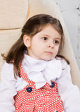 Little girl sits in an armchair Royalty Free Stock Images