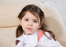 Little girl sits in an armchair Stock Image